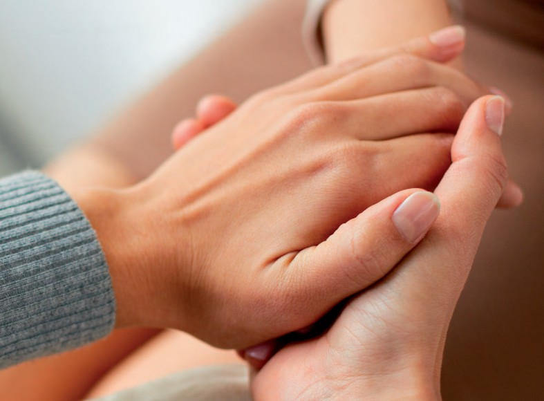 one hand clasping another in comfort
